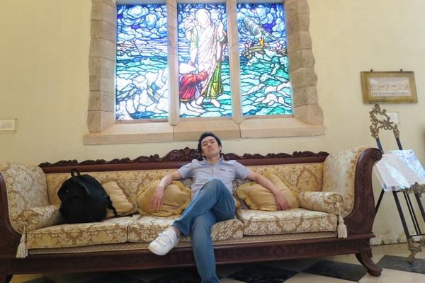 ステンドグラスとドヤ顔でソファーに座る中西浩