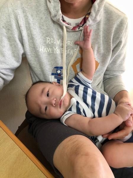 パーカーの紐をくわえる赤ん坊