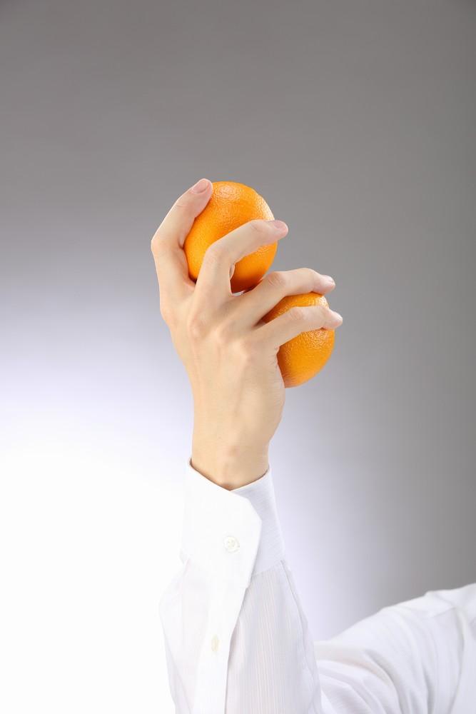 オレンジを2つ持つハンドモデルの手
